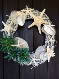 Bumpy starfish and pretty cream and white polished shells dance around a whitewashed 18 grapevine wreath adorned with 3 faux succulent plants. Perfect beach bling for your front door or gate. It also looks great laying flat on a table as a candle ring. Coastal Wreath, Nautical Wreath, Seashell Wreath, Seashell Crafts, Coastal Decor, Wreath Crafts, Diy Wreath, Grapevine Wreath, Coastal Christmas
