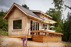 The Gambier Island Tiny Getaway is a 16' x 12' cabin on an island in British Columbia. Board and batten siding with exposed rafter tails give it a classic cabin look. Built by Click Modular Homes. https://www.facebook.com/SmallHouseBliss