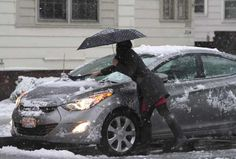 Renee Schechinger of Rochester, N.Y. brushes snow off her car on Oxford Street before heading off to work on April 23,2012.    (AP Photo/Democrat and Chronicle, Tina Yee)