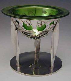 ARCHIBALD KNOX FOR LIBERTY & Co. TAZZA  Manufacturer Liberty & Co.   Designer Archibald Knox    Description Tudric polished pewter tazza with a green glass liner with typical Archibald Knox decoration   Country of Manufacture England   Date c.1904