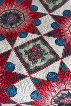 Close-up of Olde World Star. The quilt features intricate pieced stars and broderie perse.