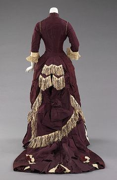 Around 1874, the style of gowns began to hug the thighs in the front while the bustle at the back was reduced to a natural flow from the waist to the train.  The dense textiles preferred were covered in trimming, beadwork, puffs and bows to visually elevate them further.  This gowns overskirt & bustle have ecru fringe the accent the 'S'-shaped silhouette.