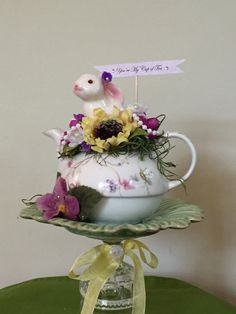 """This sweet rabbit is ready to join your Mother's Day table complete with his nest of flowers, moss, pearl beads and glitter. He's nestled in a vintage china teapot embellished with a yellow seam binding ribbon, vintage button and lots of millinery flowers that rests on top of a china plate and vintage cordial glass with his message """"Your My Cup of Tea""""    This handmade and one-of-a-kind creation measures approximately 10 """" tall and 6"""" wide.   Shop this product here…"""