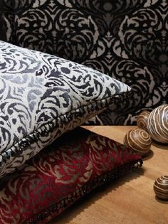 Fibre Naturelle -  Safari Fabric Collection - A black and grey screen, a red gold cushion and a grey and white cushion, all with an ornate pattern, with wooden balls