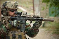 An ISAF Special Operations Team member assists with security while Afghan Local Police receive their first payments in Helmand province, Afghanistan, April 9. Afghan Local Police complement counterinsurgency efforts by assisting and supporting rural areas with limited Afghan National Security Forces presence.  U.S. Marine Corps photo by Sgt. Pete Thibodeau