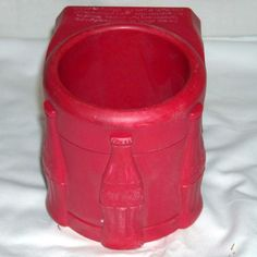 Red plastic embossed Coca-Cola cup holder that attaches to a car window, etc.