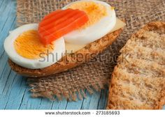 Rusk sandwich with egg and carrot on old wooden table - stock photo