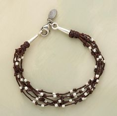 "Twig-like strands of waxed brown linen sprout etched sterling silver buds, each allowed freedom of movement between knots. Conical endcaps flank a lobster clasp. Handcrafted in USA. 7-1/2""L."