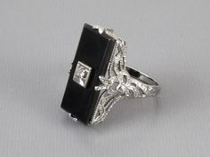 Stunning antique Art Deco 14k white gold filigree black onyx and diamond ring, size 5-1/2. With lovely feminine ribbon bow details on the