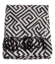 Jacquard-weave throw in soft fabric with fringe. Size 51 x 67 in.