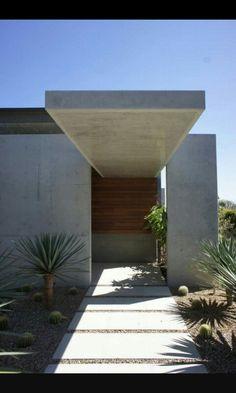 Entrada estilo moderno con porche en hormigon visto y jardin de grava