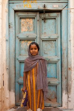 A cute Indian girl stands in front of a worn front door in Bijapur, Karnataka, India)