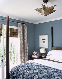 The blue print coverlet is from Urban Outfitters. Walls are painted Blue Slate by Pratt  Lambert. Curtains are Arts Decoratif by Le Gracieux. The Moroccan parchment star light is from Mosaik. Eisner designed the geode table lamp on the 19th-century walnut bedside table from Italy. Chad Eisner home.