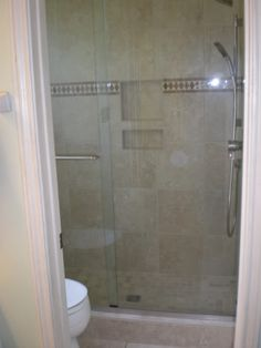Roman inspired tiled shower with Venetian bronze fixtures and a