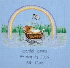 Counted cross stitch birth announcement showing a mouse floating in a moses basket under a rainbow, designed by Margaret Sherry. The kit contains:      16 count light blue Aida fabric;     stranded cottons;     needle;     chart; &     instructions  Alphabet included for personalisation. Finished Size: 22 x 22 cm