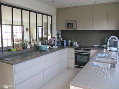 Une cuisine moderne agencée en U avec verrière d'intérieur.