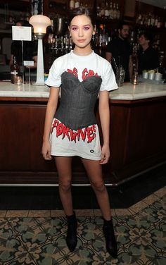 YouTube star Amanda Steele attends the Wolk Morais fashion show in LA. Got Qs about lhow to wear your newly purchased corset? (FYI, every party wardrobe needs one.) Then consider styling one over a low-key slogan tee (trousers, optional)