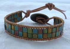 Wrap bracelet with tila beads on metallic gold leather. $35.00, via Etsy. This bracelet contains tila beads in greens and golds on metallic 2mm leather cord, with a gold tone button closure.