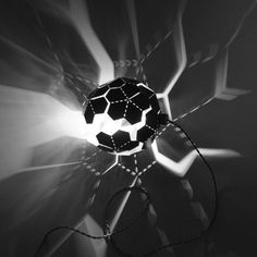 """Comet Lamp by  Elaine Fortin AND Virginia Lamothe.    """"The laser cut and perforated steel Comet is sold flat and it's up to the user to fold it into the desired shape. It can be folded into a sphere or more randomly into an organic, abstract shape."""""""