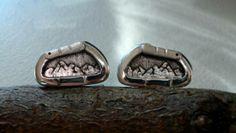 Gemelos en plata de ley con forma de mosquetón y detalles de montañas en el interior. Hechos a mano.
