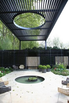 This black slat pergola is one of the most unusual designs we've encountered - the round opening in the center allows the sunlight to hit the small pool directly beneath it, while still providing diffused lighting on the patio around it. We are a Minneapolis MN #LandscapeDesign firm, and we do pergolas. http://www.aldmn.com