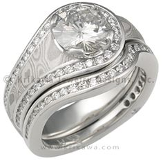 White Mokume Embrace Bridal Set - This ring is named for the way the channel set accent diamonds embrace the center stone. The diamonds come halfway down one side of the band. This is an asymmetrical design with a lot of flare. The band tapers to just over 4mm wide around bottom. With 0.24 ctw ideal cut accent diamonds. - This spectacular engagement ring is set with a moissanite. White mokume gane. It is shown with and without a diamond channel contoured wedding band.