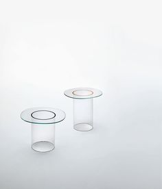 ROOUND design Victor Carrasco | Low tables available in two heights with glass top in a shape of a deformed circle, in 8 mm. thick tempered transparent extralight glass. The base is a hollow cylinder in transparent borosilicate glass. The join between the top and the base is enhanced by a coloured ring, available in the range of glossy lacquered glasses.