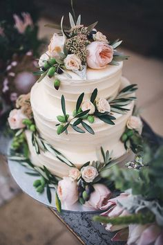 Naked 3 tier wedding cake adorned with greenery.
