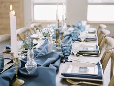 Champagne + Linen, Missoula Wedding + Event Planners, put together a styled shoot in Alberton, Montana at White Raven Wedding and Event Center. This is a picture from their contemporary wedding styled shoot that featured blue velvet and gold candlesticks. This is a picture of a place setting. There are two square plates with a folded napkin in between them and a blue watercolor and gold place card with the name