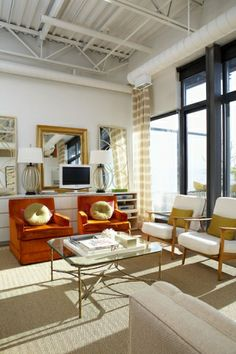 Designer Sabrina Linn transformed her urban, industrial loft space into a warm and luxurious haven through a rich blend of pattern, texture and traditionally styled, elegant furniture that is a little unexpected in this type of building. Using warm tones - orange, copper and gold accents throughout, the space exudes a warmth that contrasts so beautifully with the soaring high ceilings and open, airy windows. While the space isn't huge, the open layout and traditional gold details make it feel quite luxurious.