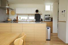 ステンレスバイブレーションとナラ柾目のコの字型キッチン