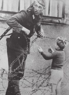 When the Berlin wall was built, this little boy was stuck on the opposite side to his family. Despite orders to not let anyone pass, this German soldier helped this boy over the barbed wire so he could get to his family. The soldiers superior saw him do this and immediately detached the soldier from his unit. no one knows what happens to the soldier afterwards. It's amazing that he risked everything just for one little boy. he's truely an extraordinary man!