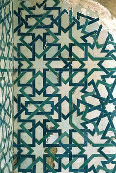 Decorated area from the Alhambra, in Granada, Spain, showing Geometric Pattern using ceramic tiles, mosaic or pottery.