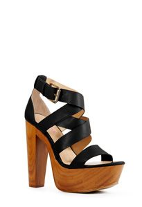 A faux wood wrapped platform with thick crossed straps and a cutout counter with an adjustable metal buckle at the ankle.
