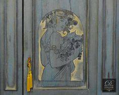 Καινοτομία αποτελεί η ζωγραφική παράσταση στο κέντρο της πόρτας, εμπνευσμένη από πίνακα του Alphonse Mucha.