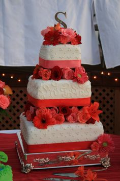 """Wedding cake in red, orange, and coral... 14"""" - 10"""" & 6"""" tiers. leaving 4"""" between tiers for flowers, the cake is wrapped in rolled fondant."""