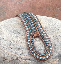 The Indian Princess (5-Row) in Stonewash Blue & Copper  Rather than 3 rows usually featured in the Indian Princess bracelet, this one is done in 5 rows of beads and leather! It features a center row of 4mm faceted glass beads in a beautiful stone washed blue, finished with a Josephine knot. It is surrounded by 2 rows of Opaque Picasso seed beads in Montana Matte Blue. The two outer rows are stitched in soft denim blue lined glass beads. The Indian Princess is adorned with an etched button…