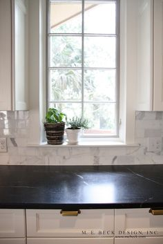 White cabinets, black countertop, marble backsplash and brass pulls = perfection!!