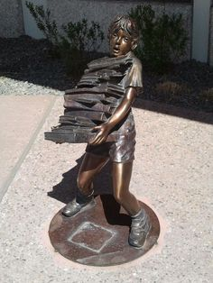 Child carrying a stack of books. Penrose Public Library, 20 North Cascade Avenue, Colorado Springs,
