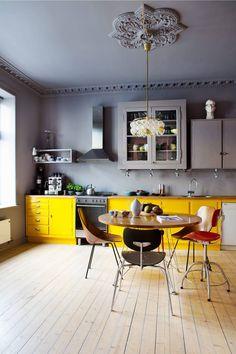 GULT OG GRÅTT: Det italienske bordet, MagisTavolo XZ3, ble kjøpt for flere år siden og har fått ny, lakket overflate. Glasskapet sto i leiligheten, det er strippet ned og pusset opp igjen. Taklampen med håndblåste kupler og ramme i messing, er kjøpt på Empire Antikk. Designstolene er kjøpt ulike steder, Medea-stoler i finer av Vittorio Nobili for Tagliabue (1955), de svarte av Jean Prouve (1930) fra Vitra, og den røde er SE68 av Egon Eiermann for Wilde + Spieth (1951).