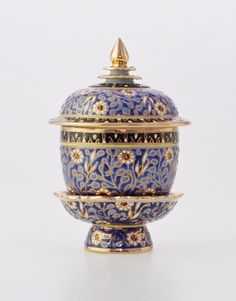 Benjarong urn with footed tray - Chakri pattern on blue An astonishing Thai porcelain with multiple layers of exquisitely hand-painted Thai arts, kiln fired on every layers of the process to bring out the best of each colors and with multiple relief glaze to emphasize its blue background against the beautiful 18k gold accent. Made with the technique of craftsmanship originally exclusive for the Thai royal court, Benjarong is the piece of true class that make an impression at first sight…