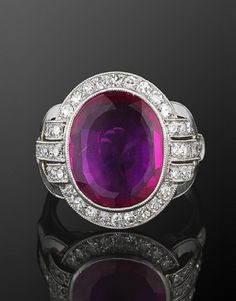 Art deco ring:  An oval Burma ruby weighing approximately 3.12 carats, is surrounded by single cut diamonds in a geometric platinum mounting.