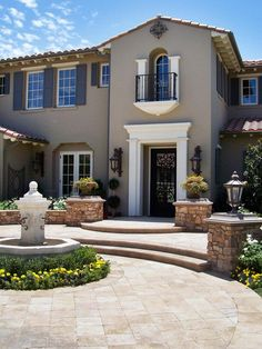 A wrought iron front door and second-floor balcony accent this home's stately gray exterior. Gorgeous stone hardscaping and a water feature complete the home's Mediterranean appeal.: