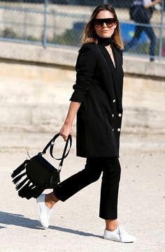 Street style look total black com bolsa franjas e tenis branco.