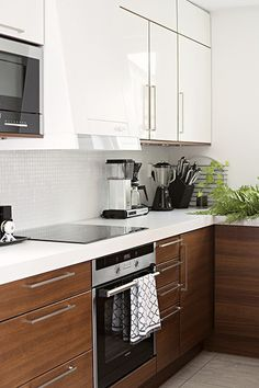 Glossy white and tainted wood, black appliances and tender greens Kitchen Redo, Kitchen Dining, Kitchen Cabinets, Two Tone Cabinets, Black Appliances, Beautiful Kitchens, Dining Area, My Dream Home, Small Spaces