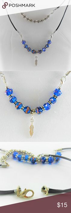 """Blue Translucent Beaded Necklace. Double corded (black) beaded necklace. Top strand has shiny silver colored beads alternated with accent/spacer beads. This section is 15"""" long and attaches to cord with lobster clasps.  Longer cord is 19.5"""" long, with black translucent blue beads, silver colored accent/spacer beads. Dainty silver colored feather accent. Lobster clasp in back.  Dainty, lovely necklace.  Hand crafted, new, never worn. Jewelry Necklaces"""