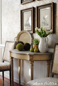 Beautiful carved table, wallpaper, old pictures, and lovely chairs...elegant entrance.