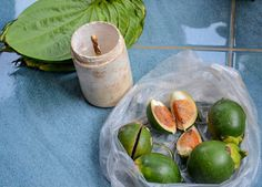 Bag of areca nut, tub of limestone paste and bai plu betel leaves. Chewing Betel Nut in Rural Thailand Isaan with gummy old grannies. Ingredients of betel chewing include Areca nut, betel leaf and sandstone paste. Traditions and Culture in rural Thailand (Isaan) by http://potatoinrice.com/