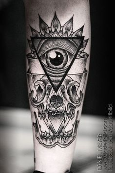 A human eye encased in a triangle and sacred geometry sits above a grinning animal skull in this tattoo by Daniel Meyer