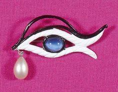 * Schiaparelli - Broche oeil dessinée par Jean COCTEAU (vers 1938) en fonte peinte en blanc, pupille en pâte de verre bleue pervenche, sourcils laqués noirs, le tout rehaussé d'une perle blanche en forme de goutte